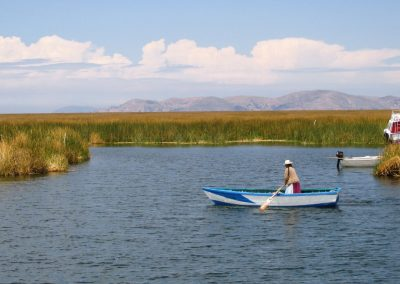 An Uros woman rowing near the floating islands, Puno